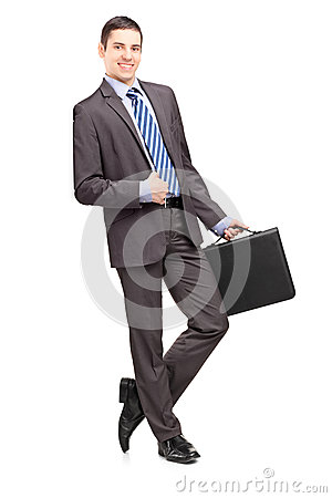 Smiling businessman holding a leather briefcase and leaning agai