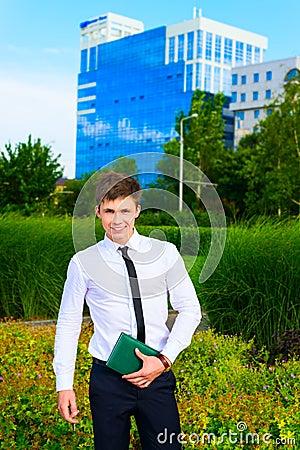 Smiling businessman holding notebook