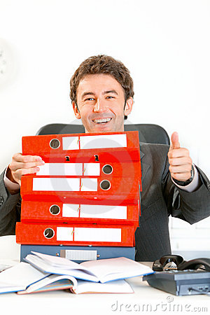 Smiling businessman looking out from folders
