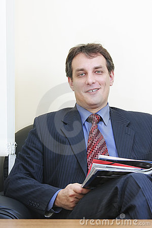 Smiling businessman with magazine
