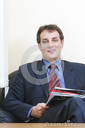 Smiling businessman with magazine