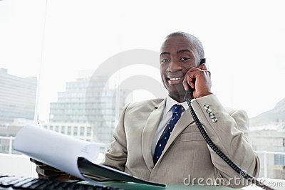 Smiling businessman on the phone while reading a document