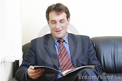 Smiling businessman reading magazine