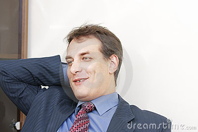 Smiling businessman scratching head