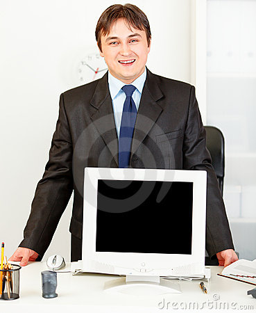 Smiling businessman showing monitors blank screen