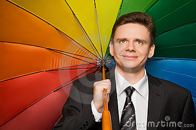 Smiling businessman in suit with umbrella