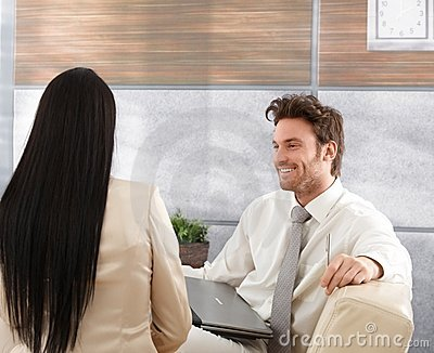 Smiling businessman talking to woman Stock Photo