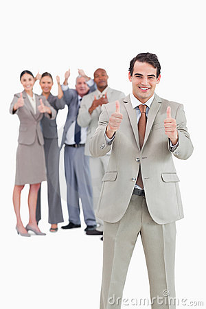 Smiling businessman with team behind him