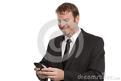 Smiling businessman texts on cell phone
