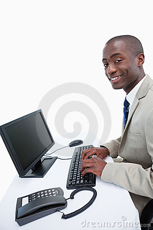A smiling businessman using a computer