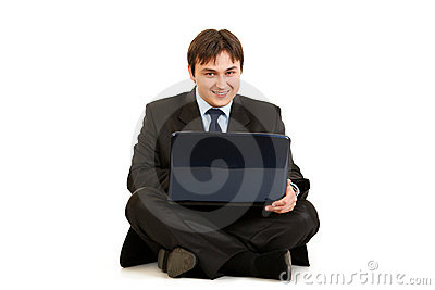 Smiling businessman working on laptop on floor