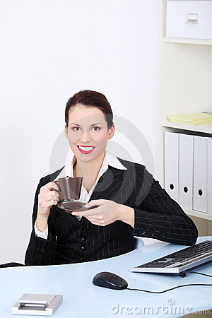 Smiling businesswoman drinking coffee.