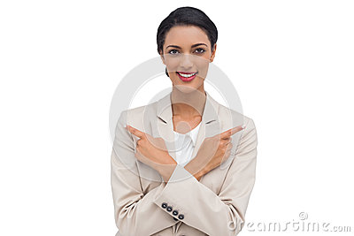 Smiling businesswoman with her arms crossed and fingers pointing