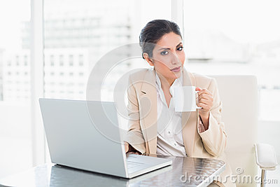 Smiling businesswoman holding mug while working on laptop