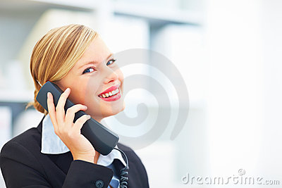 Smiling businesswoman holding a telephone