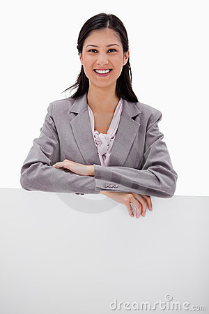 Smiling businesswoman leaning on blank wall