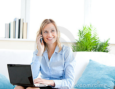 Smiling businesswoman phoning and using her laptop