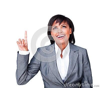 Smiling businesswoman pointing upwards