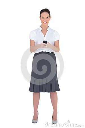 Smiling businesswoman sending a text message