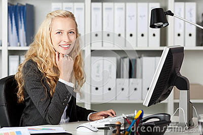 Smiling Businesswoman Using Computer At Desk