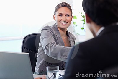Smiling businesswoman welcomes customer