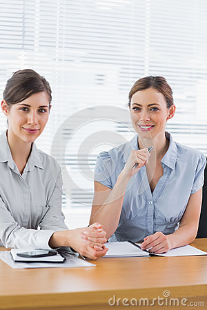 Smiling businesswomen working together and looking at camera