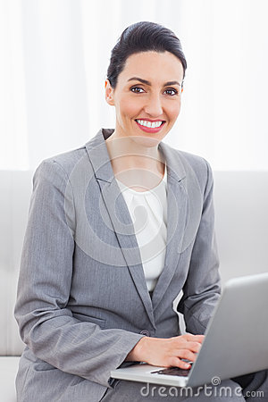 Smiling busineswoman using laptop sitting on sofa