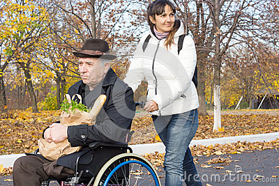 Smiling carer pushing an old man in a wheelchair stock photo image - Smiling Carer Pushing An Old Man In A Wheelchair Stock