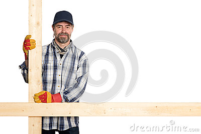 Smiling carpenter holding the planks