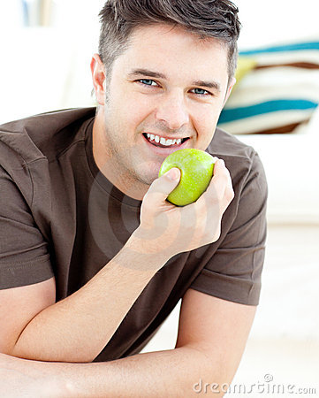 Smiling caucasian man holding an apple smiling