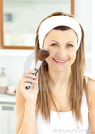 Smiling caucasian woman putting powder on her face