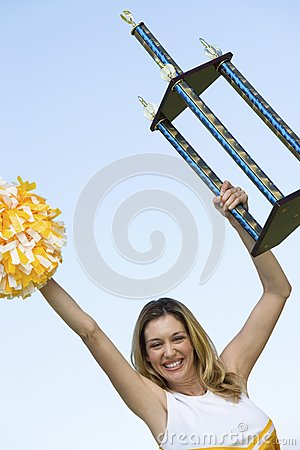 Smiling Cheerleader holding trophy