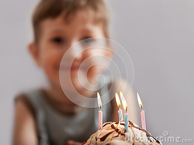 Smiling child with birthday cake candle