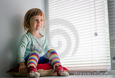 Smiling child looking out the window