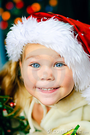 Smiling child in Santa s hat  has a Christmas