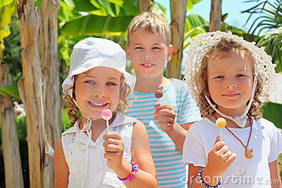Smiling children three together eat lollipop