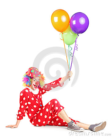 Smiling clown sitting and holding balloons