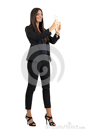 Free Smiling Corporate Woman In Formal Black Suit Taking Photo With Cellphone Royalty Free Stock Photos - 61295168