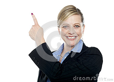 Smiling corporate woman pointing upwards