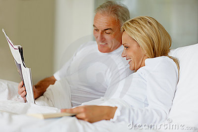Smiling couple in bed reading a book together