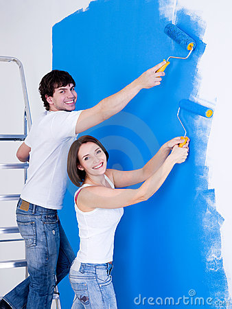 Smiling couple brushing the wall