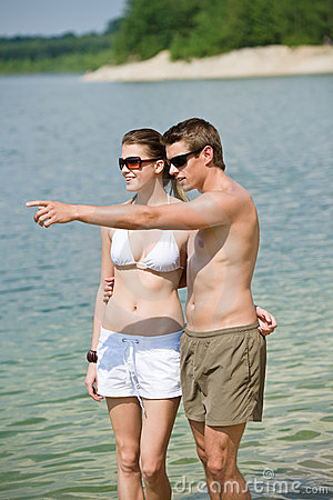 Smiling couple enjoy sun at seashore in water