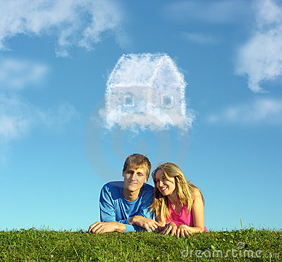 Smiling couple on grass and dream cloud house