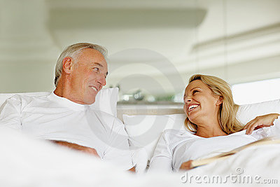 Smiling couple having fun while relaxing in bed