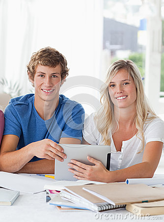 A smiling couple hold a tablet