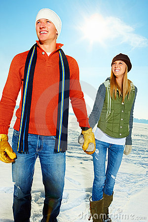 Smiling couple holding hands out on the snow