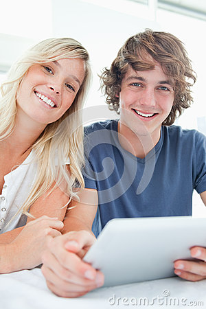 Smiling couple holding a tablet and looking at the camera