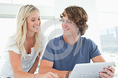 Smiling couple holding a tablet and looking at each other