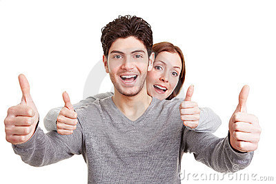 Smiling couple holding thumbs up