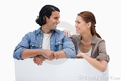 Smiling couple leaning on blank wall